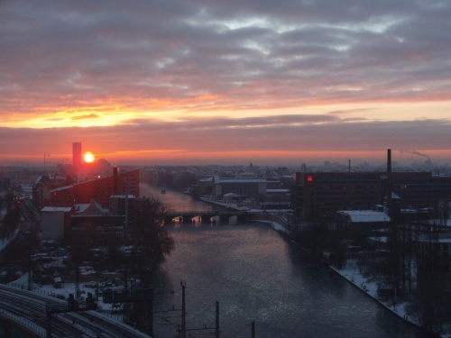 Blick über die Stadt bei Sonnenuntergang, in der Mitte ein Fluß mit einer Brücke