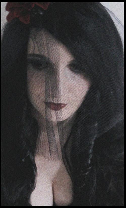 Portrait einer Frau mit schwarzen Haaren, schwarzer Bluse, schwarzem durchsichtigen Schleier und schwarz geschminkten Augen..