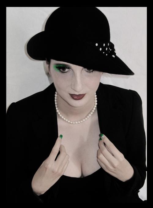 Portrait einer Frau mit schwarzem Hut, schwarzem Kleid, schwarz geschminkten Augen
