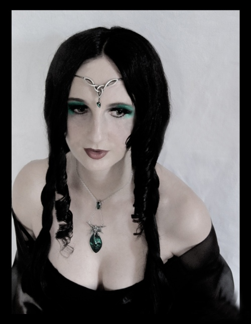 Portrait einer Frau mit schwarzen Haaren, schwarzem Kleid und Silberschmuck auf Stirn und Brust