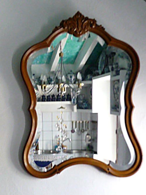 Ein Spiegel in einem geschwungenen Rahmen. Er zeigt eine Küche.