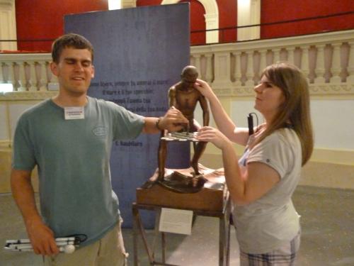 Eine junge Frau ertastet eine Skulptur
