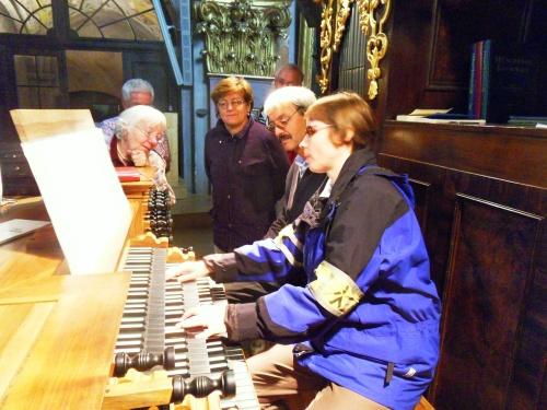 Eine Frau spielt Orgel. Fünf Menschen hören aufmerksam zu.