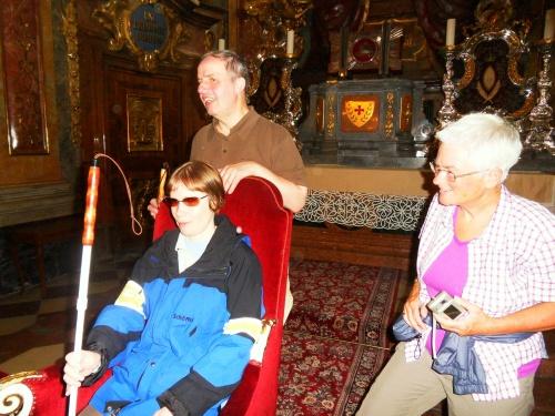 Drei Menschen vor dem Barockaltar des Doms, eine Frau sitz auf einem prächtigen Stuhl.
