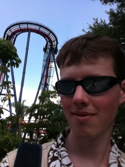 Portraitfoto eines jungen Mannes, im Hintergrund eine Achterbahn