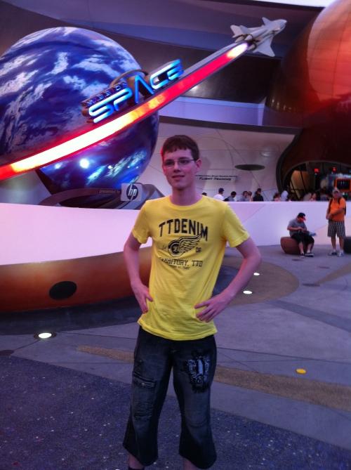 Ein junger Mann posiert vor einer Jahrmarktsattraktion