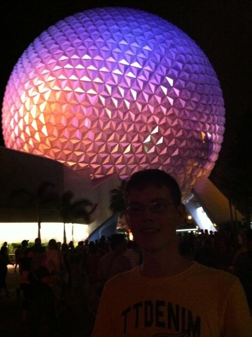 Junger Mann vor einer großen, kugelförmigen Architektur