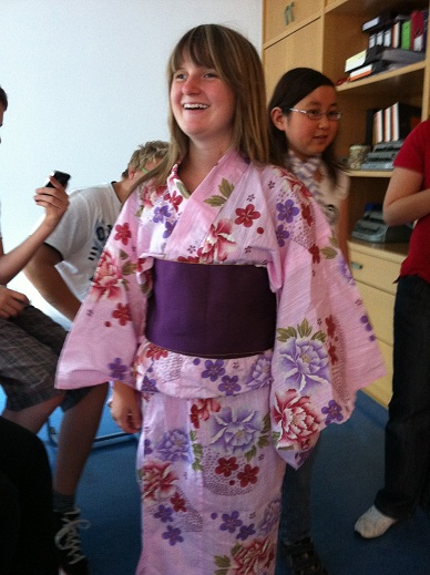Eine lachende Frau im rosa Kimono, um die mehrere Leute herumlaufen.