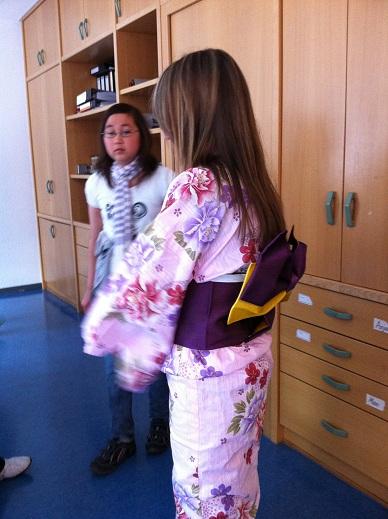 Eine Frau im rosa Kimono, mit einer anderen jungen Frau.