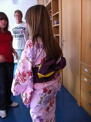 Eine Frau im rosa Kimono, mit einer jungen Frau und einem jungen Mann.