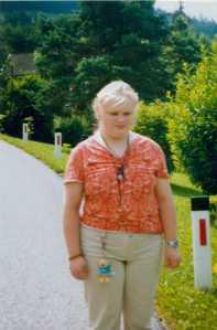 Eine junge Frau am Rand einer Landstraße stehend