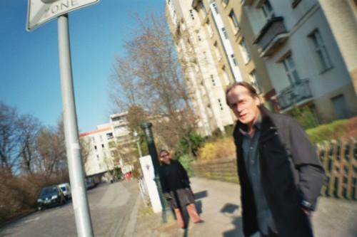 Zwei Passanten an einer Bushaltestelle