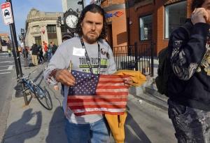 """Ein Mann hält eine verschmutzte US-amerikanische Fahne in die Kamera. Er steht auf einer sonnigen Straße. Auf seinem Sweat-Shirt steht """"Tough Ruck 2006""""."""