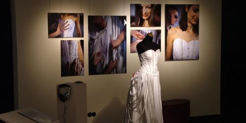 Kleiderpuppe mit langem schwarz-weißen Kleid. Im Hintergrund großformatige Fotos der Ausstellung