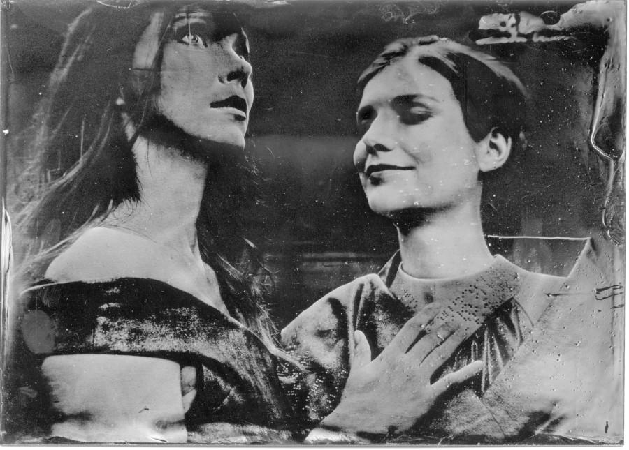 Eine junge Frau befühlt das Kleid einer anderen jungen Frau mit kurzen Haaren, die ihre Augen geschlossen hat. Schwarz-Weiß
