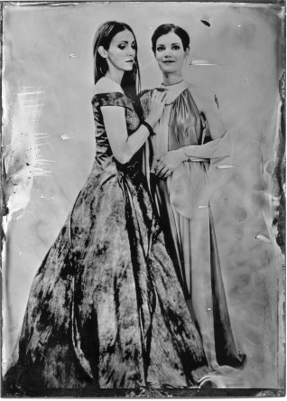 Zwei junge Frauen eine mit langen und eine mit kurzen Haaren in langen Ballkleidern. Schwarz-Weiß