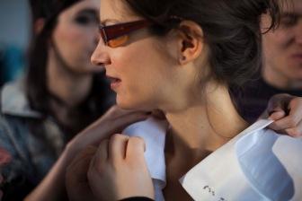 Eine Frau im Seitenprofil dreht den Kopf nach links. Die Kamera ist nah bei ihr und zeigt nur ihr Gesicht und ihren zarten Hals. Die Augen sieht man hinter dem Brillenbügel nicht mehr, der Mund ist leicht geöffnet, doch es gibt kein Lächeln. Eine Frau hinter ihr hält zwischen Daumen und Zeigefinger den steif gestärkten Kragen des weißen Kleides. Ihre Fingernägel sind schwarz lackiert. Mit der anderen Hand berührt sie den Kragen von der anderen Seite. Vorne ertasten die Finger von zwei kleinen Frauenhänden den vorderen Teil des Kragens. (Aljoscha Khairetdinov)