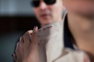 Die rechte Hand einer Frau mit schwarz lackierten Fingernägeln berührt ganz behutsam die roten Buchstaben der Brailleschrift, die entlang der linken Schulterklappe eines weißen Hemdes gestickt sind. Die Frauenhand berührt die Buchstaben mit dem Zeige-, Mittel- und Ringfinger. Der Daumen und der kleine Finger hängen in der Luft, als würde sie Klavier spielen. Dahinter steht ein Mann mit einer Sonnenbrille. Lächelt er, hört er zu, wartet er? (Aljoscha Khairetdinov)