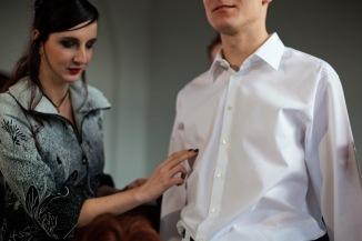 Eine Frau in einem grau-schwarz gemusterten Oberteil steht neben einem schlanken Mann im weißen Hemd. Die Frau mit spitzen, dunkel lackierten Fingernägeln berührt mit ihrer rechten Hand das Hemd des Mannes, schaut aber nicht in seine Richtung, sondern nach unten. Sie berührt leicht seine Brust. (Ewa Maria Slaska)
