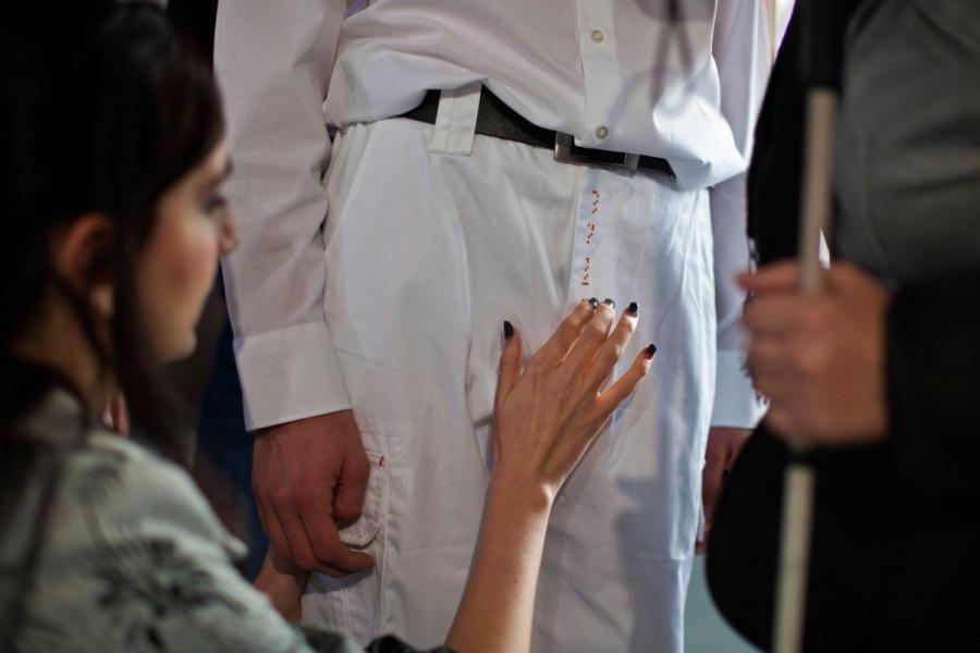Ein Mann im weißen Hemd, weißer Hose und schwarzem Gürtel mit metallener Schnalle, steht zentral im Bild. Eine schwarzhaarige Frau kniet neben ihm. Von ihr sieht man im rechten Profil nur den Arm und die rechte Hand mit lackierten Nägeln. Von ihm sieht man lediglich den Unterkörper, vom Oberschenkel hin bis zur Taille. Er steht regungslos, mit beiden Armen an der Hosennaht. Die Frau berührt ganz leicht den Hosenschlitz der weißen Hose, die mit kleinen roten Punkten bestickt ist. Vor dem Mann in Weiß steht eine dunkel angezogene Person, die in der linken Hand einen Blindenstock hält. (Ewa Maria Slaska)