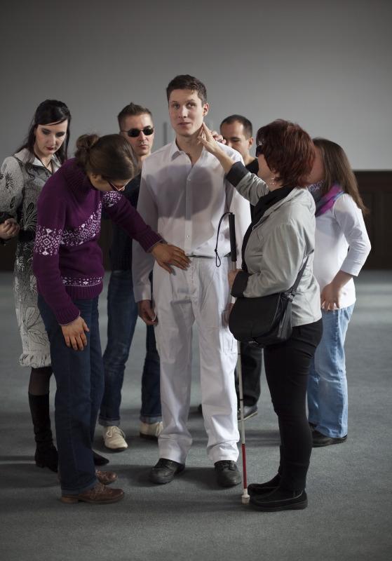 Sechs Menschen stehen um einen jungen Mann herum, wie die Zahlen auf dem Zifferblatt einer Uhr. Die Frau mit dem Blindenstock auf 5 Uhr berührt den jungen Mann am Hals links unterm Kinn. Es befinden sich ein Mann auf 1 Uhr, eine Frau auf 3 Uhr, eine Frau in einem grau-schwarz gemusterten Kleid auf 9 Uhr und ein Mann mit einer Sonnenbrille auf 11 Uhr. Eine Frau auf 7 Uhr ist leicht gebeugt. Sie trägt eine Brille. Ihre linke Hand berührt mit den Fingern den Hosenlatz des jungen Mannes in der Mitte. Er ist größer als alle anderen, steht entspannt da, scheint aber leicht irritiert. (Aljoscha Khairetdinov)