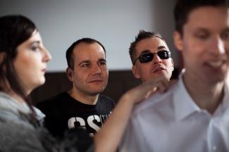 Drei Männer und eine Frau. Ein Mann in weißem Hemd steht am vorderen rechten Bildrand. Sein Gesicht ist angeschnitten und verschwommen. Dennoch wird deutlich, dass er der wichtigste Protagonist der Szene ist. Er lächelt sehr breit. Zwei Männer hinter ihm, obwohl besser sichtbar, sind nur Zuschauer. Ein Mann mit nach oben gegeltem Haar trägt eine schwarze Sonnenbrille. Der andere scheint ganz andächtig auf die Hände der Frau zu schauen, die links steht und sehr konzentriert etwas auf der Schulter des Mannes im weißen Hemd ertastet. Man sieht sie im rechten Profil. Sie wirkt wie eine blasse Indianerin mit rot geschminktem Mund. (Ewa Maria Slaska)