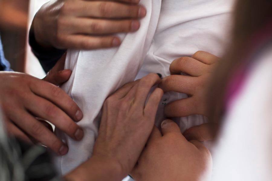Eine Nahaufnahme. Man sieht nur einen Teil eines Hemdes und fünf Hände, die den Stoff ertasten.
