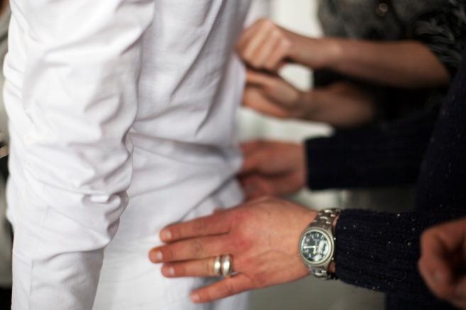 Man sieht einen Mann in Weiß von hinten und vier Hände, die den Stoff ertasten. Zwei Hände im Hintergrund gehören einer Frau. Die zwei Hände im Vordergrund einem Mann. Dieser trägt eine große Uhr und zwei massive silberne Ringe.