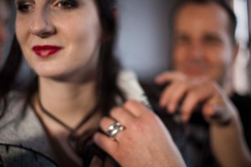 Eine Frau mit schwarzen langen Haaren und braunen Augen steht im Vordergrund des Bildes. Sie lächelt und scheint in Bewegung zu sein. Das Bild ist etwas verschwommen. Im rechten Teil sind die Hände der Menschen, die neben dem Model stehen und fühlen, was sie trägt. Am Ringfinger der Hand, die in Richtung ihrer Halskette fasst, befinden sich zwei glänzende silberne Ringe. Im Hintergrund sind sehr verschwommen die Umrisse eines Mannes mit kurzen braunen Haaren zu sehen. (Sophia Stolf)
