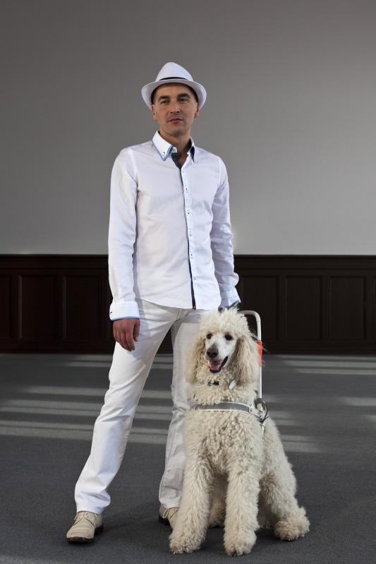 Ein Mann steht mit einem weißen Königspudel im Führgeschirr in einem leeren Raum. Weiße Wände, ein schwarzes Holzpaneel zieht sich die Wand im unteren Drittel entlang. Auf dem grauen Boden bilden Sonnenlichtflecken das Fenster nach. Der Mann steht leicht breitbeinig und mit hängender Hand da. Er hat einen leichten Bartschatten und trägt ein Hemd, dessen Kragen offen steht, einen Hut, der aus Stroh sein könnte und eine weiße Jeans, dazu weiße Halbschuhe im Turnschuhstil. Der Hund befindet sich in Sitzposition, er hechelt, sein Maul steht offen. (Niki Matita)