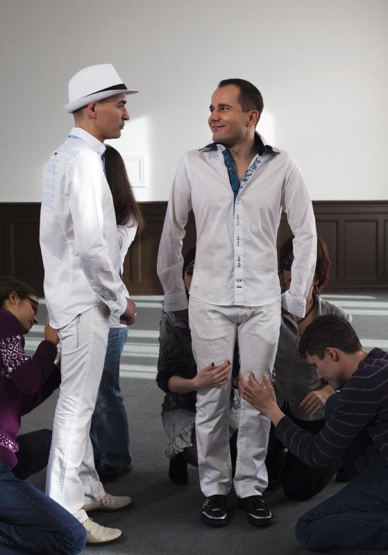 Zwei junge Männer ganz in weiß gekleidet mit Hemd und Hose. Einer trägt weiße Schuhe, der andere schwarze. Der mit den weißen Schuhen steht links und ist nur von der Seite zu sehen. Er trägt einen weißen Hut im Panamastil. Der mit den schwarzen Schuhen steht frontal zu uns und wendet dem anderen sein strahlendes Gesicht zu. Die Hände haben beide mit einem Finger in die Hosentaschen gesteckt. Um die beiden herum knien mehrere Leute, die sehr mit ihren Beinen beschäftigt sind. Beim uns zugewandten Mann werden gerade die Knie befühlt, er hat zwei Hände auf dem Oberschenkel. Beim anderen wird eher der hintere Hosenbund untersucht. (Katrin Heidorn)