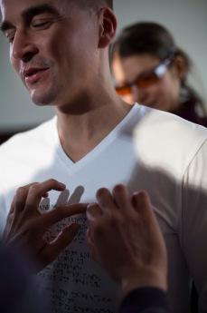 Der Oberkörper eines Mannes, sehr nah, als ob er direkt vor uns steht. Zwei schlanke Hände tasten die Punktschrift, die auf der Brust seines weißen T-Shirts aufgestickt ist. Im Hintergrund sieht man unscharf eine Frau mit orangefarbener Brille. Der Mann hat die Augen geschlossen, sein Mund ist zu einem verzückten Lächeln gespitzt. (Karl Ahl)