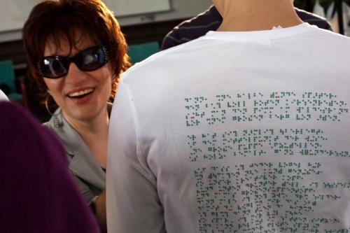 Links lacht uns eine Frau mit Sonnenbrille an. Ein sehr sympathisches, strahlendes Lachen. Rechts neben ihr ist der Rücken eines Mannes mit weißem T-Shirt, auf dem ein Text in grüner Punktschrift mit vereinzelten roten Punkten steht. (Karl Ahl)