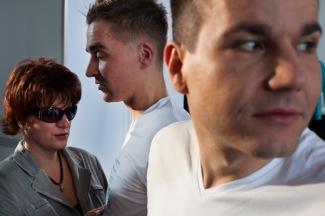 Eine Dreierszene. Rechts im Vordergrund ist unscharf ein Mann, der über seine Schulter zum Bild hinaus sieht. Links im Hintergrund ist ein Mann und eine um einen Kopf kleinere Frau mit Sonnenbrille zu sehen. Sie berührt sehr zart seine Brust. Auf seinem T-Shirt erkennt man einen Punktschrifttext. Die Szene hat etwas Geheimnisvolles. Was verbindet die drei Leute? (Karl Ahl)