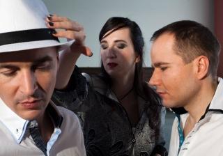 Drei Menschen mit geschlossenen Augen. Links ein Mann im weißen Hemd, am Kragen blau abgesetzt, mit schwarz-weißer Knopfleiste. Er trägt einen weißen Panamahut mit schwarzem Hutband. Sein Gesicht ist der Kamera zugewandt. Rechts ein Mann, dunkelblond, im Profil, kurze Haare. Auch er trägt ein weißes Hemd mit farbig abgesetzter Knopfleiste, diesmal türkisblau, mit schwarz hinterlegtem Kragen. Im Hintergrund in der Mitte eine Frau im Kleid mit zarten, weißen Muster auf schwarzem Grund. Ihre langen dunklen Haare hängen links und rechts auf den Kragen ihres Kleides. Über der Stirn liegt ein modisch seitlich geschwungener Pony. Ihr Mund ist dunkelrot geschminkt. Ihre Augen tragen reizvollen grauschwarzen Lidschatten. Ihr dünner Arm greift von hinten an das schwarze Hutband und befühlt es mit zartgliedrigen Fingern. Die werden durch schwarzen Nagellack betont. Ein konzentriertes und zugleich sinnliches Bild. (Katrin Heidorn)