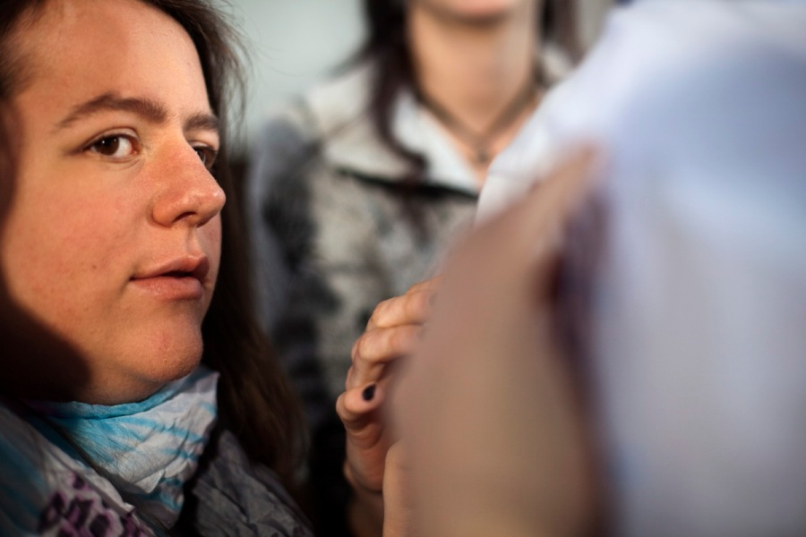 Zwei Frauen stehen neben einer Person im weißen Hemd, von der wir aber nur einen großen Teil des Rückens sehen. Die beiden Frauen berühren das Hemd jeweils mit ihrer rechten Hand. Die Hand der Frau im Schal drängt so nah in den Vordergrund.