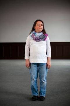 Eine Frau in hellen Jeans und weißem Pullover. Sie trägt ein markantes buntes Seidentuch, das ihrer ansonsten eher schlichten Kleidung etwas Besonderes verleiht. Sie hat langes, braunes Haar, das ihr über den Rücken fällt und trägt Ohrringe. Sie blickt zum rechten Bildrand. Vielleicht ist sie ein wenig verlegen oder gespannt was passiert? Sie scheint konzentriert darauf, dass sie gerade fotografiert wird und nimmt den Raum für sich ein. Im Hintergrund sind verschwommen die Wände des großen Saals zu sehen. (Sophia Stolf)