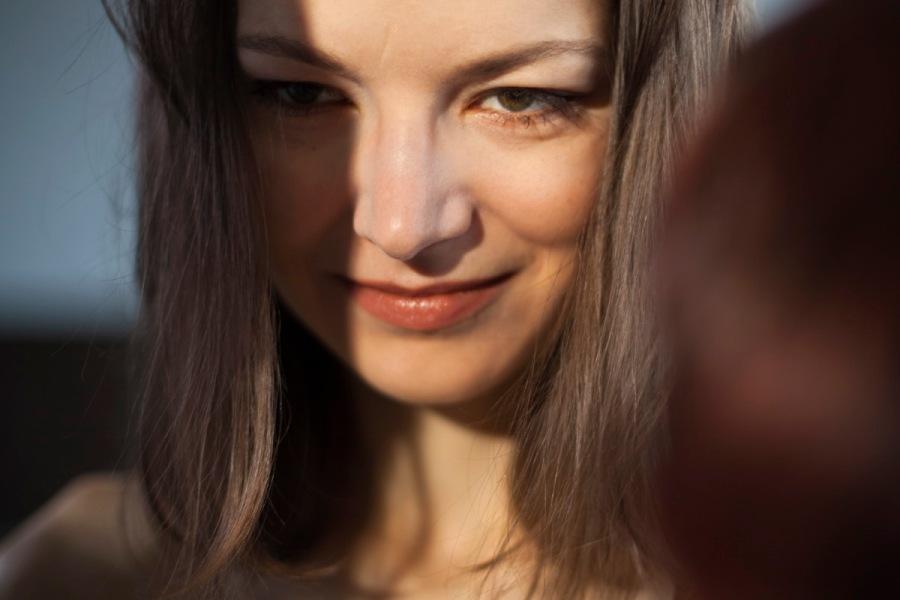 Eine wunderschöne junge Frau. Dunkelblond mit braunen Augen. Nur das Gesicht, der Hals und die nackte Schulter sind zu erkennen. Halblange Haare umrahmen das Gesicht. Sie lächelt anmutig, tugendhaft. (Ewa Maria Slaska)