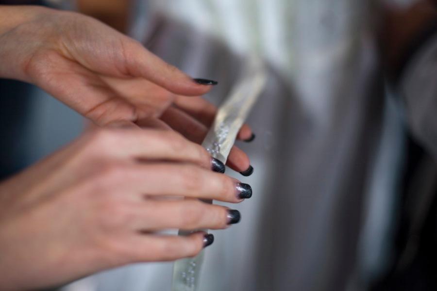 Von links kommen zwei auffallend lange zarte Frauenhände ins Bild, die einen weißen Streifen Stoff halten. Der Streifen ist auf ganzer Länge weiß bestickt. Er gehört zu einem Kleidungsstück, das schemenhaft undeutlich im Hintergrund zu sehen ist. Die Hände sind blass und gepflegt. Die scheinbar echten langen Fingernägel sind schwarz lackiert. Wir sehen die linke Handfläche und den rechten Handrücken. Sie halten ganz locker und zart den Streifen Stoff. Nur ein Finger berührt direkt die Stickerei. Der Streifen, den sie halten, verschwindet unscharf im Hintergrund. (Katrin Heidorn)