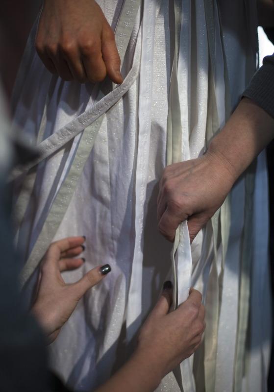 Vier Hände betasten die weißen Streifen an einem Kleid. Zwei der Hände, die unterschiedlichen Personen gehören. Eine zarte mit dunkel lackierten Fingernägeln und eine breitere werden sich vielleicht die nächsten Augenblicke begegnen. Eine Hand hängt herunter. Ob sie wohl zu der Person in dem Kleid gehört? (Sophia Stolf)