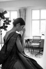 Eine kurzhaarige Frau im Abendkleid sitzt halb von der Kamera abgewandt nachdenklich auf einem Stuhl. Schwarz-Weiß