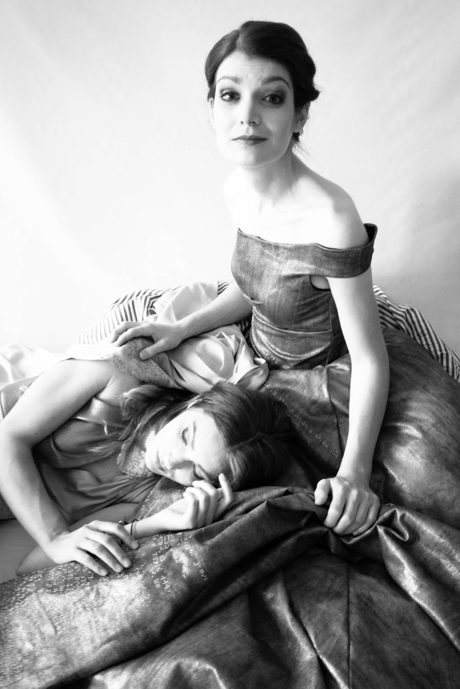 Eine junge, lanhaarige Frau liegt mit dem Kopf im Schoß einer jungen, kurzhaarigen Frau in einem trägerlosen Kleid. Schwarz-Weiß
