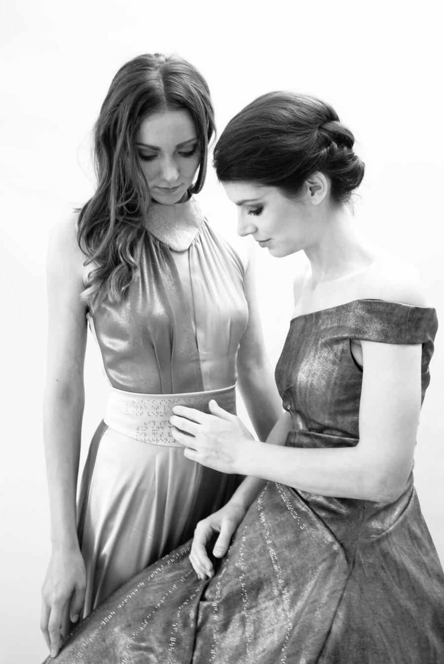 Zwei junge Frauen in Abendkleidern schauen einander an und befühlen ihre Kleider. Schwarz-Weiß