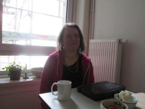 Eine Frau sitzt am Tisch vor einem Fenster
