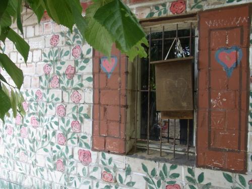 Ein vergittertes Fenster, mit gemalten Fensterläden in einer mit Blumen bemalten Wand