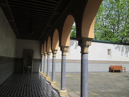 Ein steinerner Hof von einem arabisch aussehenden Säulengang aus gesehen