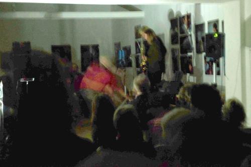 Eine Bühne in einem nahezu dunklen Raum, auf der man im Hintergrund schemenhaft zwei Musikerinnen erkennt. Im Vordergrund ebenso schemenhaft das Publikum.