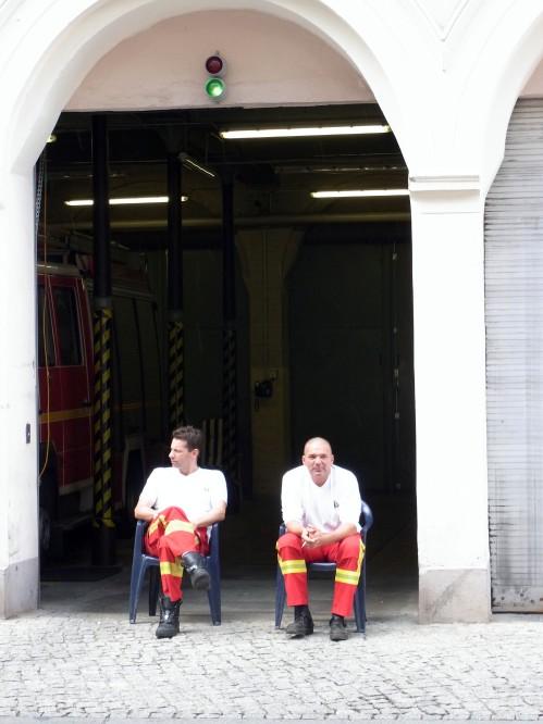 Zwei Feuerwehleute sitzen vor einer Toreinfahrt in der Sonne