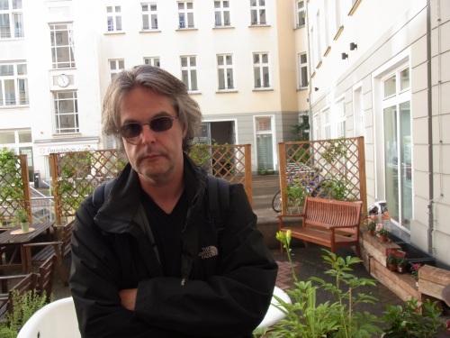Ein Mann mit Sonnenbrille steht mit verschränkten Armen in einem Innenhof