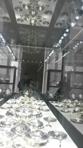 Eine langgestreckte hell erleuchtete Vitrine mit Silbergeschirr in einem ansonsten abgedunkelten Raum